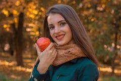 Το νέο χαριτωμένο κορίτσι με το κόκκινο κραγιόν στα χείλια και τα θερμά χαμόγελα μαντίλι σας κρατά την κινηματογράφηση σε πρώτο π Στοκ Φωτογραφίες