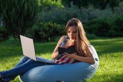 Το νέο χαριτωμένο κορίτσι με το lap-top, κάθεται στην τσάντα φασολιών στον κήπο ή το πάρκο, στην πράσινη χλόη καναπές έννοιας που Στοκ Εικόνες