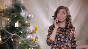 Το νέο χαριτωμένο όμορφο κορίτσι μιλά με κινητό τηλέφωνο κοντά στο χριστουγεννιάτικο δέντρο γιορτάστε τη φθορά santa μητέρων καπέ φιλμ μικρού μήκους