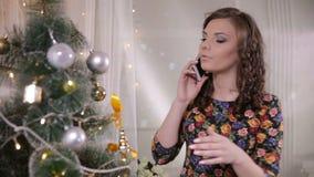 Το νέο χαριτωμένο όμορφο κορίτσι μιλά με κινητό τηλέφωνο κοντά στο χριστουγεννιάτικο δέντρο γιορτάστε τη φθορά santa μητέρων καπέ απόθεμα βίντεο