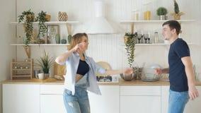 Το νέο χαρούμενο ζεύγος έχει τη διασκέδαση χορεύοντας στην κουζίνα στο σπίτι απόθεμα βίντεο