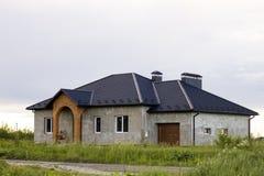 Το νέο χτισμένο μην βιωμένο ακόμα γκρίζο σπίτι ένας-καταστημάτων με την επικεράμωση της στέγης, πλαστικά παράθυρα, επικονίασε του στοκ εικόνες