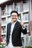 Το νέο όμορφο άτομο απολαμβάνει on-line στο κινητό τηλέφωνο με την πιστωτική κάρτα στοκ εικόνες