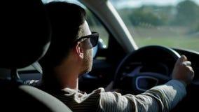 Το νέο όμορφο άτομο κάθεται σε ένα αυτοκίνητο μόνο και κινείται πέρα από την εθνική οδό στην ηλιόλουστη ημέρα, οπισθοσκόποι καθρέ φιλμ μικρού μήκους