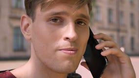 Το νέο όμορφο άτομο μιλά στο τηλέφωνο στο πάρκο στην ημέρα το καλοκαίρι, προσέχοντας στη κάμερα, έννοια επικοινωνίας, που θολώνετ απόθεμα βίντεο