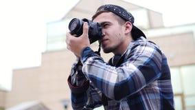Το νέο όμορφο άτομο παίρνει τη φωτογραφία της κάμερας με τη κάμερα και χαμογελά φιλμ μικρού μήκους