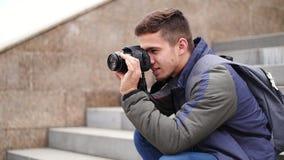 Το νέο όμορφο άτομο παίρνει τη φωτογραφία της κάμερας με τη κάμερα και χαμογελά απόθεμα βίντεο