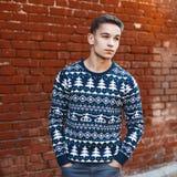 Το νέο όμορφο άτομο πλέκει το πουλόβερ με τις διακοσμήσεις Χριστουγέννων επάνω Στοκ εικόνα με δικαίωμα ελεύθερης χρήσης