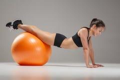 Το νέο, όμορφο, αθλητικό κορίτσι που κάνει τις ασκήσεις σε ένα fitball Στοκ Φωτογραφίες