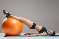 Το νέο, όμορφο, αθλητικό κορίτσι που κάνει τις ασκήσεις σε ένα fitball Στοκ εικόνα με δικαίωμα ελεύθερης χρήσης
