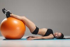 Το νέο, όμορφο, αθλητικό κορίτσι που κάνει τις ασκήσεις σε ένα fitball Στοκ εικόνες με δικαίωμα ελεύθερης χρήσης