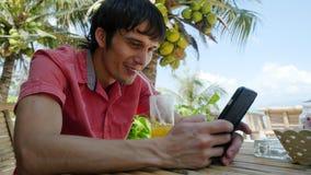 Το νέο όμορφο ευτυχές άτομο χρησιμοποιεί το έξυπνο τηλέφωνο ενώ έχοντας πίνει το κοκτέιλ σε μια τροπική θέση με τους φοίνικες Στοκ Φωτογραφίες