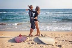 Το νέο όμορφο ζεύγος των φίλων αγκαλιάζει από τον ωκεανό με τις ιστιοσανίδες στην άμμο, αθλητισμός στοκ εικόνες