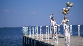 Το νέο, όμορφο ζεύγος newlyweds περπατά στην όμορφη αποβάθρα, ο νεόνυμφος κρατά τα μπαλόνια στο χέρι του, εξετάζει κάθε ένα απόθεμα βίντεο