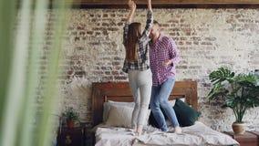 Το νέο όμορφο και αγαπώντας ζεύγος χορεύει στο κρεβάτι στο σπίτι, οι απρόσεκτοι άνθρωποι έχουν τη διασκέδαση και το γέλιο απροσεξ απόθεμα βίντεο