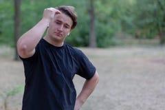 Το νέο όμορφο καυκάσιο άτομο αγγίζει την τρίχα, πράσινο εγκαταλειμμένο υπόβαθρο πάρκων στοκ φωτογραφία