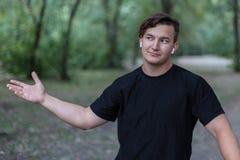 Το νέο όμορφο καυκάσιο άτομο με τη βέβαια έκφραση κάνει τη χειρονομία με το ανοικτό χέρι, που προσκαλεί για τη συζήτηση ή το διάλ στοκ φωτογραφία