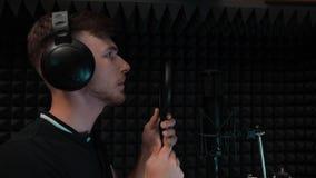 Το νέο όμορφο καυκάσιο αγόρι προετοιμάζεται για το τραγούδι καταγραφής Άτομο τραγουδιστών στο τραγούδι έναρξης ακουστικών στο στο φιλμ μικρού μήκους