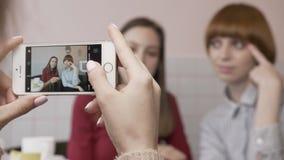 Το νέο όμορφο καυκάσιο κορίτσι κάνει μια φωτογραφία στο smartphone δύο φίλων της που κάθονται σε έναν καφέ Τα κορίτσια είναι φιλμ μικρού μήκους