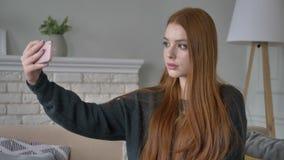 Το νέο όμορφο κοκκινομάλλες κορίτσι εφήβων χρησιμοποιεί ένα smartphone, κάνει selfie, εγχώρια άνεση στο υπόβαθρο 60 fps απόθεμα βίντεο