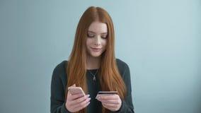 Το νέο όμορφο κοκκινομάλλες κορίτσι κάνει μια αγορά τις σε απευθείας σύνδεση, σε απευθείας σύνδεση τραπεζικές εργασίες χρησιμοποι απόθεμα βίντεο