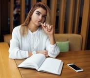Το νέο όμορφο κορίτσι γράφει στο σημειωματάριο Στοκ Εικόνες