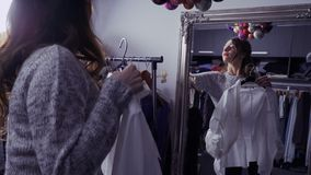 Το νέο όμορφο κορίτσι εξετάζει τον καθρέφτη και επιλογή των ενδυμάτων για το ειδικό γεγονός απόθεμα βίντεο