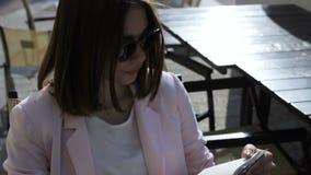 Το νέο όμορφο κορίτσι διαβάζει ένα βιβλίο, υπαίθριο απόθεμα βίντεο
