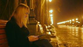 Το νέο όμορφο κορίτσι κάθεται σε έναν πάγκο σε ένα πάρκο και χρησιμοποίηση νύχτας μιας ταμπλέτας Αλέα και φω'τα στο υπόβαθρο κλεί απόθεμα βίντεο