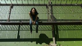 Το νέο όμορφο κορίτσι κάθεται στη σκουριασμένη γέφυρα μετάλλων πέρα από το πράσινο νερό φιλμ μικρού μήκους