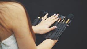 Το νέο όμορφο κορίτσι κρατά ένα σύνολο βουρτσών για τη σύνθεση Σύνολο βούρτσας makeup σε μια μαύρη περίπτωση δέρματος ότι το κορί απόθεμα βίντεο