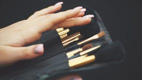 Το νέο όμορφο κορίτσι κρατά ένα σύνολο βουρτσών για τη σύνθεση Σύνολο βούρτσας makeup σε μια μαύρη περίπτωση δέρματος ότι το κορί φιλμ μικρού μήκους