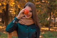 Το νέο όμορφο κορίτσι κρατά τη μεγάλη Apple κοντά στην κινηματογράφηση σε πρώτο πλάνο ματιών Στοκ Φωτογραφία