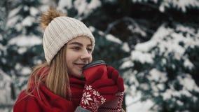 Το νέο όμορφο κορίτσι μέσα στα θερμά ενδύματα standinh κοντά στα χριστουγεννιάτικα δέντρα στο χιόνι και πίνει τον καφέ από το φλυ φιλμ μικρού μήκους