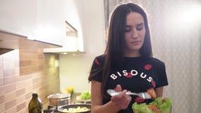 Το νέο όμορφο κορίτσι μαγείρεψε μόλις μια φρέσκια σαλάτα του πράσινων μαρουλιού και των ντοματών Απολαμβάνει του γούστου των τροφ απόθεμα βίντεο