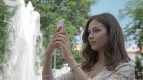 Το νέο όμορφο κορίτσι με μακρυμάλλη παίρνει μια εικόνα της στο τηλέφωνο Στο πάρκο πόλεων, κοντά στην πηγή φιλμ μικρού μήκους