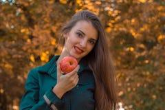 Το νέο όμορφο κορίτσι με μακρυμάλλη κρατά τη Apple στο χέρι και την κινηματογράφηση σε πρώτο πλάνο χαμόγελού του Στοκ φωτογραφία με δικαίωμα ελεύθερης χρήσης