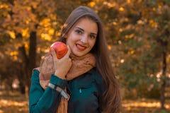 Το νέο όμορφο κορίτσι με μακρυμάλλη σε ένα σκοτεινό πουκάμισο και ένα θερμό μαντίλι κρατά τη Apple φαίνεται προς τα εμπρός χαμόγε Στοκ Φωτογραφία