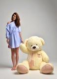 Το νέο όμορφο κορίτσι με μεγάλο teddy αντέχει το μαλακό ευτυχές χαμόγελο παιχνιδιών Στοκ Φωτογραφία