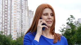 Το νέο όμορφο κορίτσι με την κόκκινη τρίχα περπατά μέσω της πόλης το καλοκαίρι και μιλά στο τηλέφωνο απόθεμα βίντεο