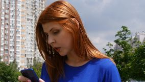 Το νέο όμορφο κορίτσι με την κόκκινη τρίχα, στην πόλη, βρήκε τις πληροφορίες στο κινητά τηλέφωνο και το χαμόγελο απόθεμα βίντεο