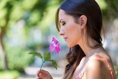 Το νέο όμορφο κορίτσι μυρίζει τα λουλούδια, ενάντια στον πράσινο θερινό κήπο Στοκ εικόνα με δικαίωμα ελεύθερης χρήσης