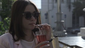 Το νέο όμορφο κορίτσι πίνει ένα κρύο ποτό, υπαίθριο απόθεμα βίντεο