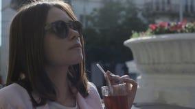Το νέο όμορφο κορίτσι πίνει ένα κρύο ποτό, υπαίθριο φιλμ μικρού μήκους
