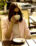 Το νέο όμορφο κορίτσι πίνει ένα φλυτζάνι του καυτού ποτού, υπαίθριο Στοκ Φωτογραφία