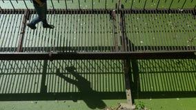 Το νέο όμορφο κορίτσι περπατά στη λεπτή σκουριασμένη γέφυρα μετάλλων πέρα από το πράσινο νερό φιλμ μικρού μήκους