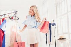 Το νέο όμορφο κορίτσι που επιλέγει και που προσπαθεί στα φορέματα στο κατάστημα στοκ εικόνες