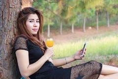 Το νέο όμορφο κορίτσι που πίνουν το χυμό από πορτοκάλι και το νέο θηλυκό δηλώνουν φανερά Στοκ εικόνες με δικαίωμα ελεύθερης χρήσης