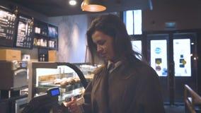 Το νέο όμορφο κορίτσι σε έναν καφέ ψωνίζει φιλμ μικρού μήκους