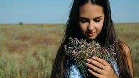 Το νέο όμορφο κορίτσι σε ένα μπλε φόρεμα απολαμβάνει τη στέπα λουλουδιών Μια νέα γυναίκα σε ένα λιβάδι στέπα Ανθίζοντας ηλιόλουστ φιλμ μικρού μήκους